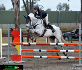 Jumping over the orange fire jump in the 90cm - 1m Open held at the Sydney International Equestrian Centre was Lois Fleming riding her beautiful horse Balboa.