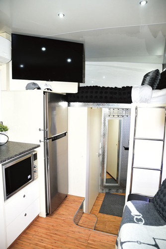 """The full sized house fridge is a feature of the living. This is a view from the living looking back through the bathroom towards the mirror door to the horse section with the second queen sized bed above the bathroom. There is no dining table in the living. """"I spoke to Tyrone about that,"""" says Ali """"and he thought it would be too crowded if there was a dining table, because there is no slide out. We have a portable table that is stored behind the fridge if we need it."""""""