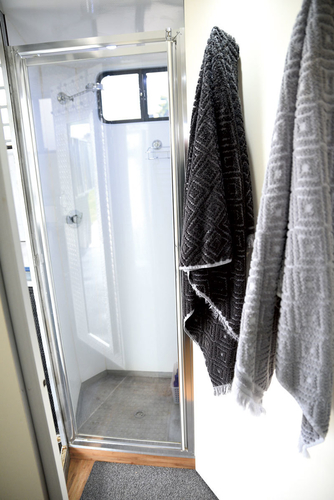 The toilet door opens and locks into the side of the shower to form the bathroom wall.