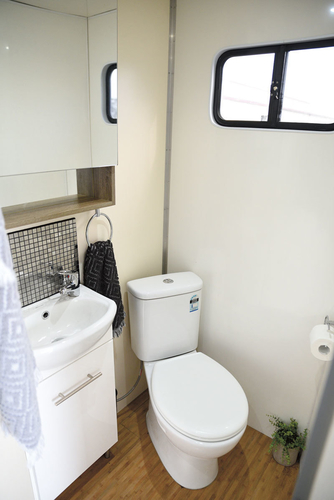 The hand basin and proper household china toilet occupy one side of the bathroom. The truck carries 200 litres of fresh water and has a grey and black water tank. If plugged into mains water the plumbing for the bathroom, kitchen and outside tap works from the one inlet.