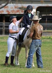 A family affair … Emma Whitley and her pony Amaranda Stormy gets some last minute tweaks from mum and dad.
