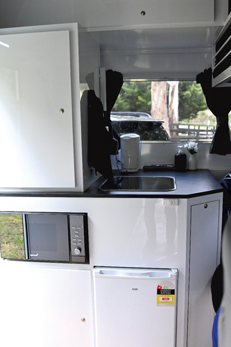 The kitchen with sink, microwave and 70L fridge is located in the nose of the float.