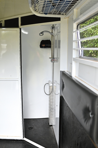"The shower room with electric hot water. ""This is wonderful, as we can keep the whole float warm and we just get out of bed and go and have a shower, all in the warm."" The shower room also provides storage and especially wet storage because of the rubber floor and drain. The float carries 61L of water."