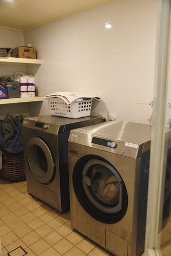 The laundry and store room within the indoor building is home to a Miele industrial washer and dryer. This room has bifold doors separating the machines from the surrounding area.