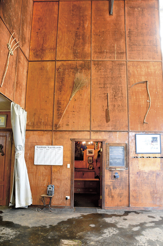 A view inside Mark's barn with antique farm tools arranged on the walls.