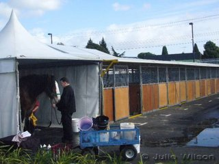 A temporary wash bay at the end of a row of portable stables. All horse facilities are built so they can be dismantled after each show.