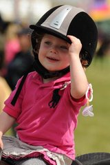 Two year old, Molly Malerba from Mt Evelyn holds on to her hat as she makes the most of her time in the saddle on a sunny Friday at Geelong Show.