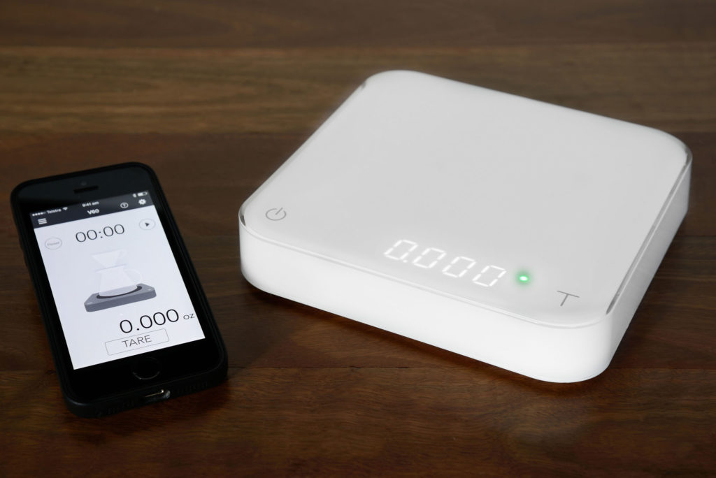 The Acaia Scale with an iphone displaying the app.