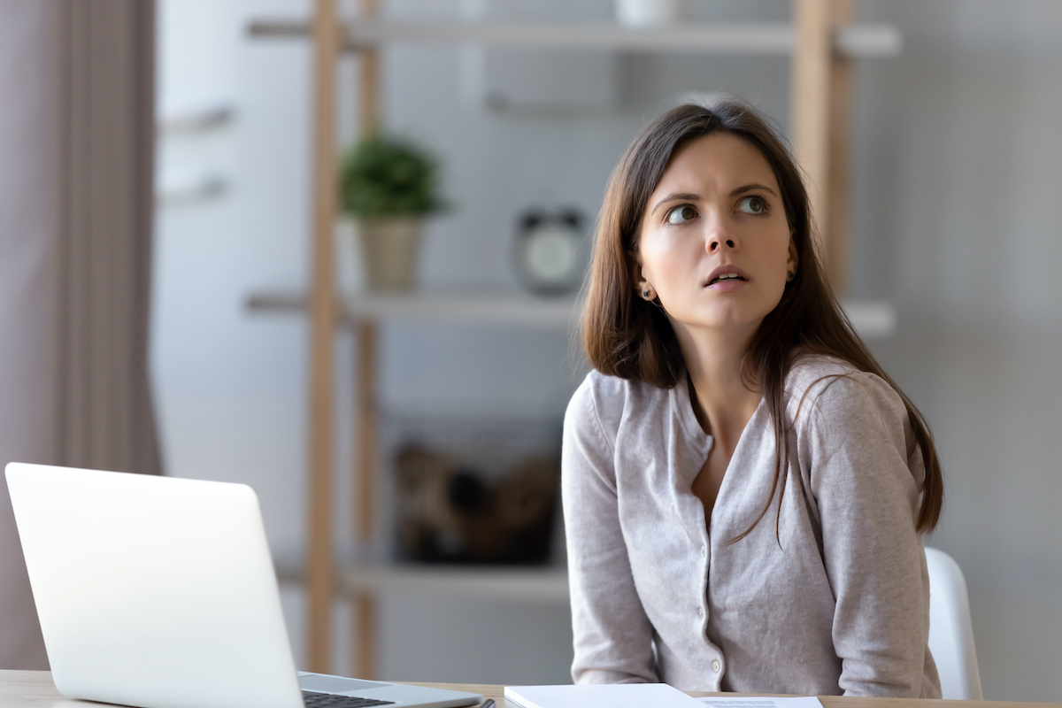 Confused woman at office home desk working at laptop looking at clock