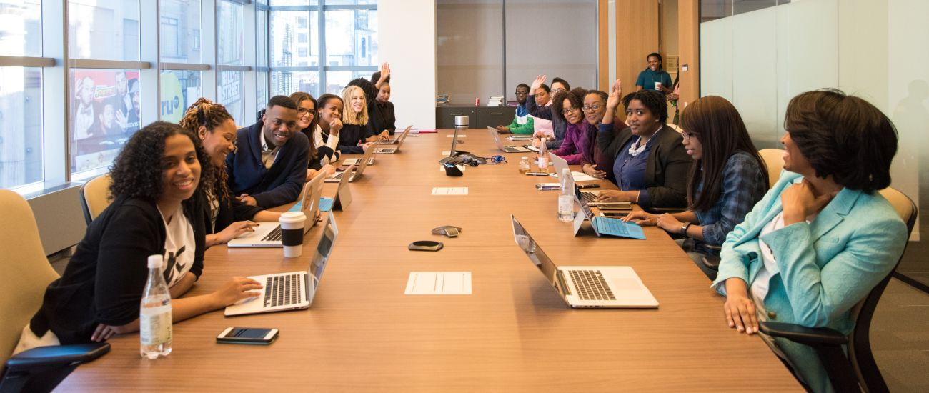 A long table hosting a meeting with a diverse staff