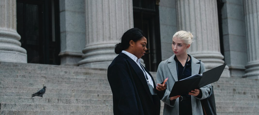 Two women meeting out the front of a courtroom looking at a binder