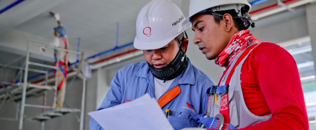 Two engineering in hard hats looking at a design