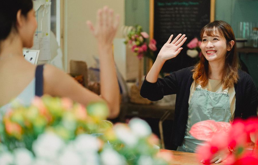 Female hospitality worker waving to a customer