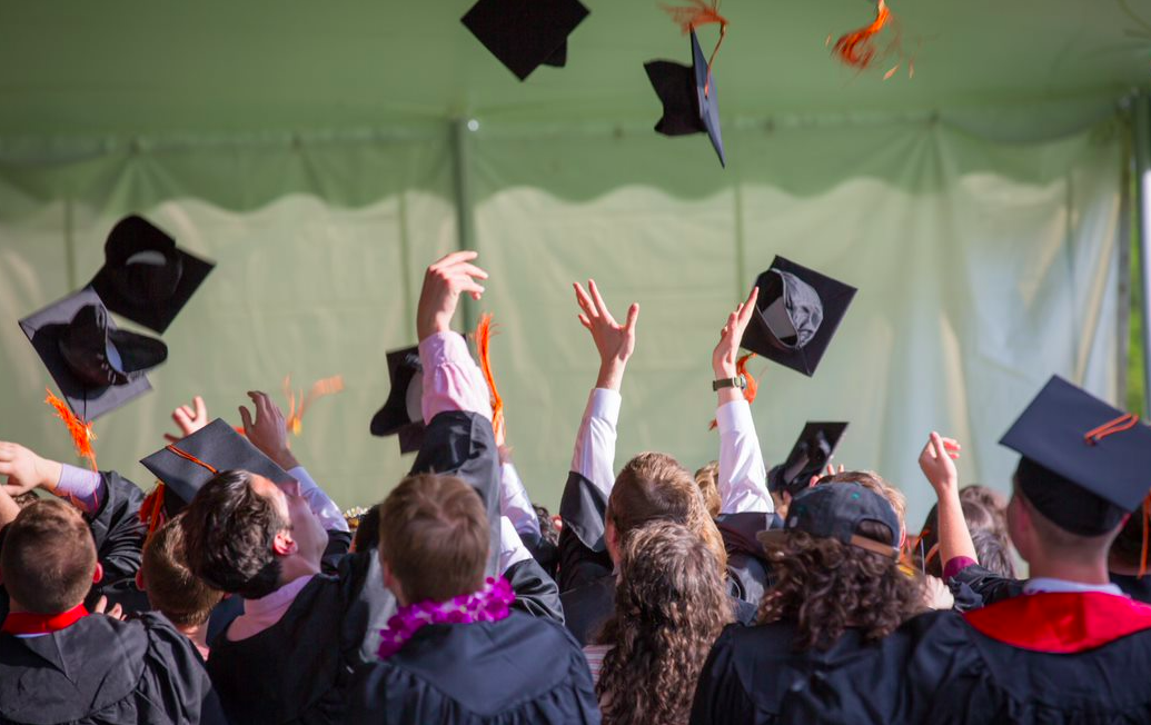 A group of graduate students dressed in gowns throwing their mortarboard hats in the air.