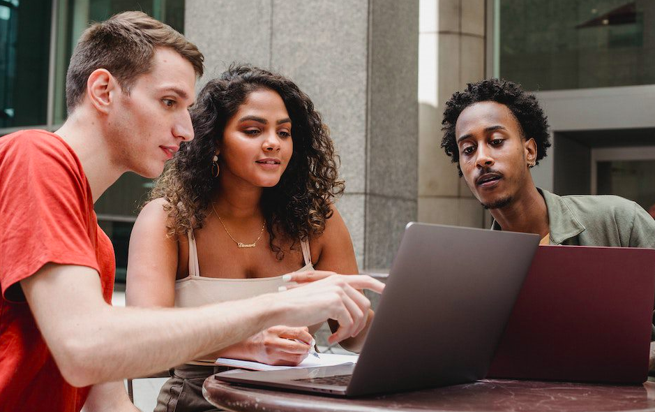 Two male and one female student sitting in front of a laptop and using LinkedIn