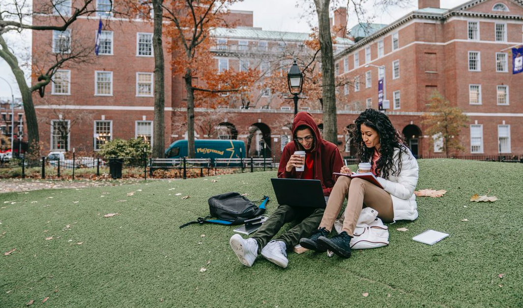 Two university students sitting on grass looking at books and a laptop.