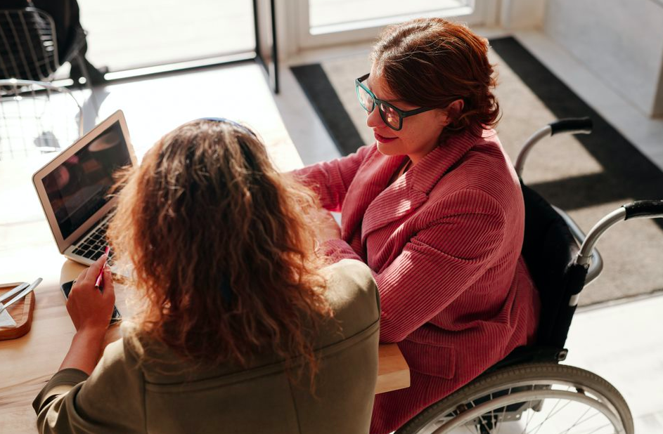 Career coach sitting with a client in front of a laptop