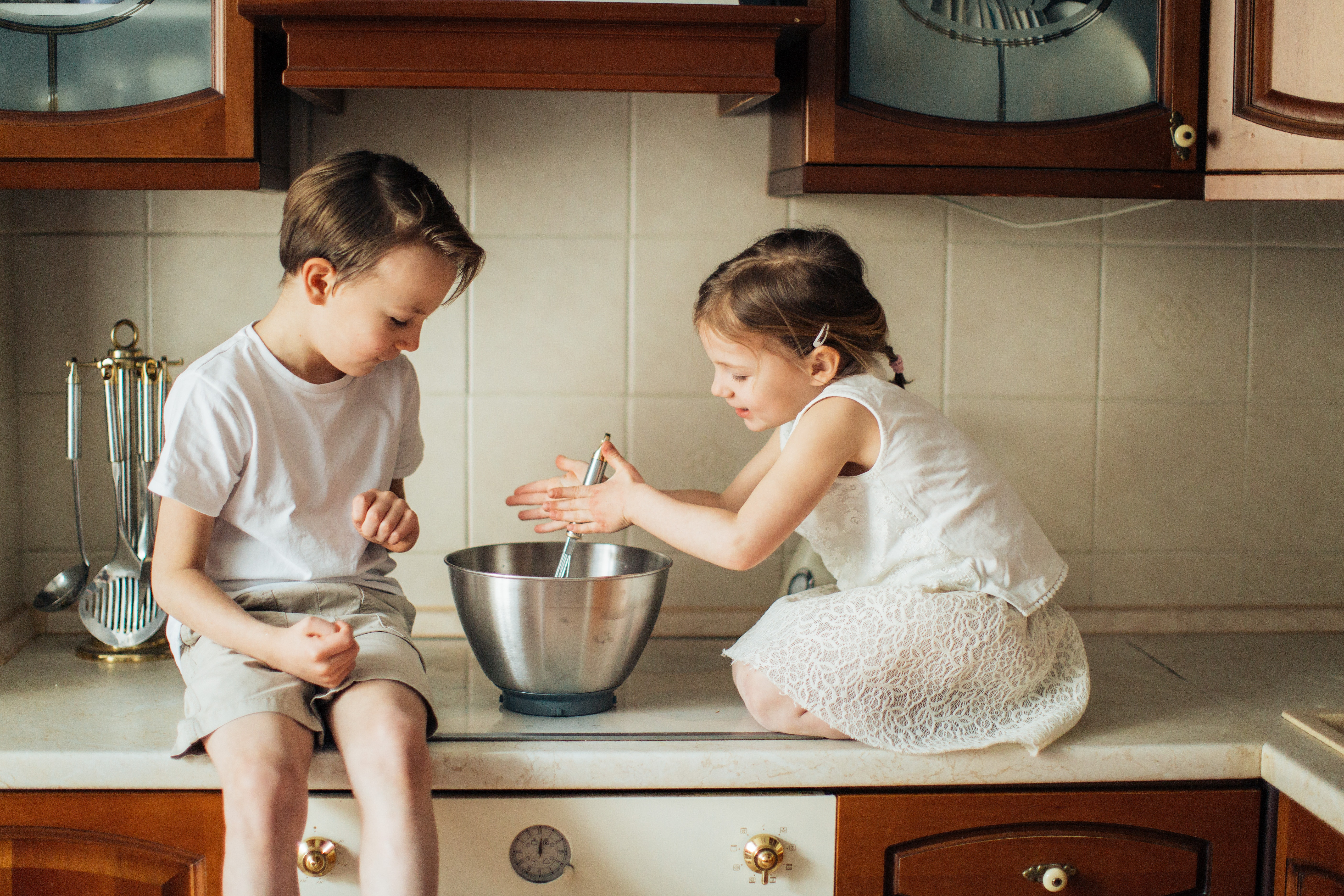 a young boy and a young girl sitting on a kitchen bench with a mixing bowl.