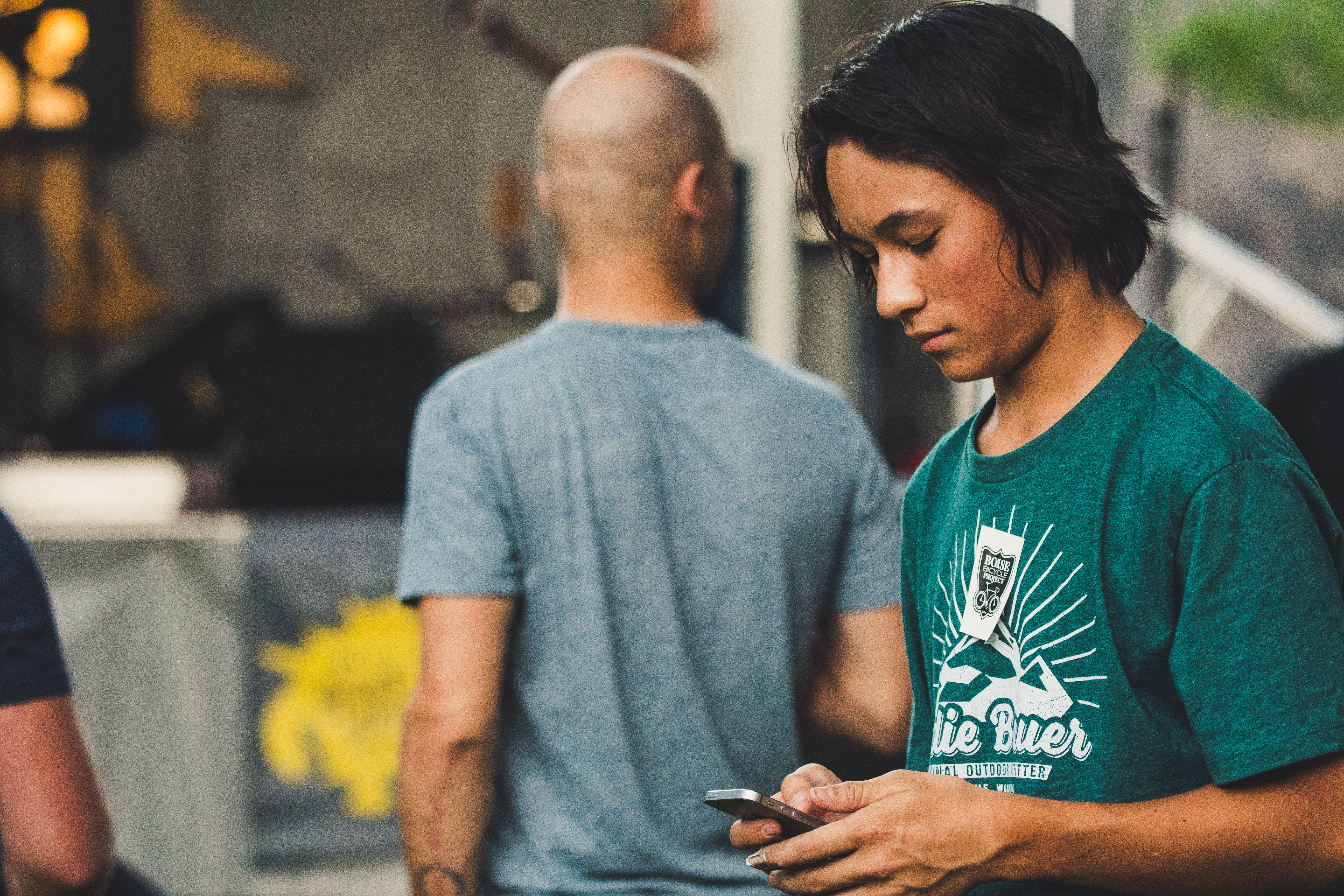 young teenager in green shirt looking down at phone
