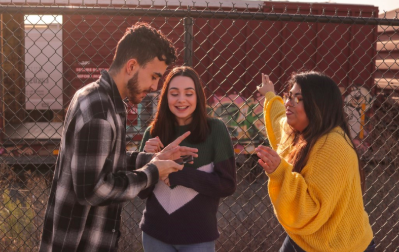 One make and two female teenagers smiling and laughing while the male uses a phone