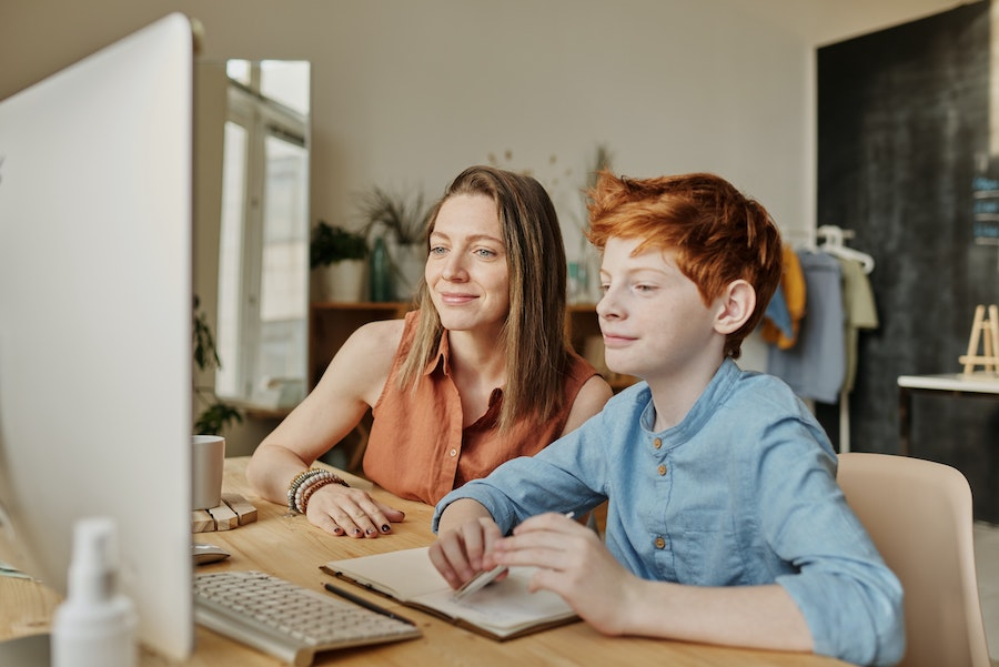 blonde woman with red haired boy sitting at a computer, both smiling
