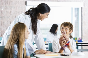 mum and teacher at school speaking to smiling young boy