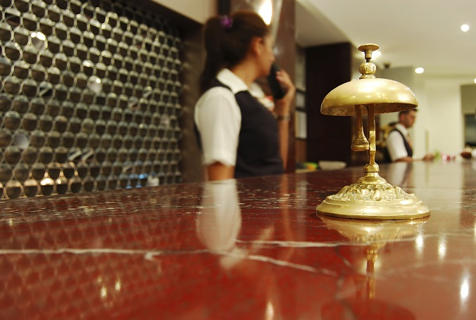Female concierge stands behind desk at reception