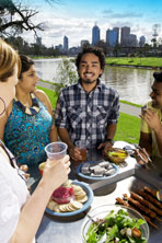 Group of people have a picnic on the banks of the Yarra River