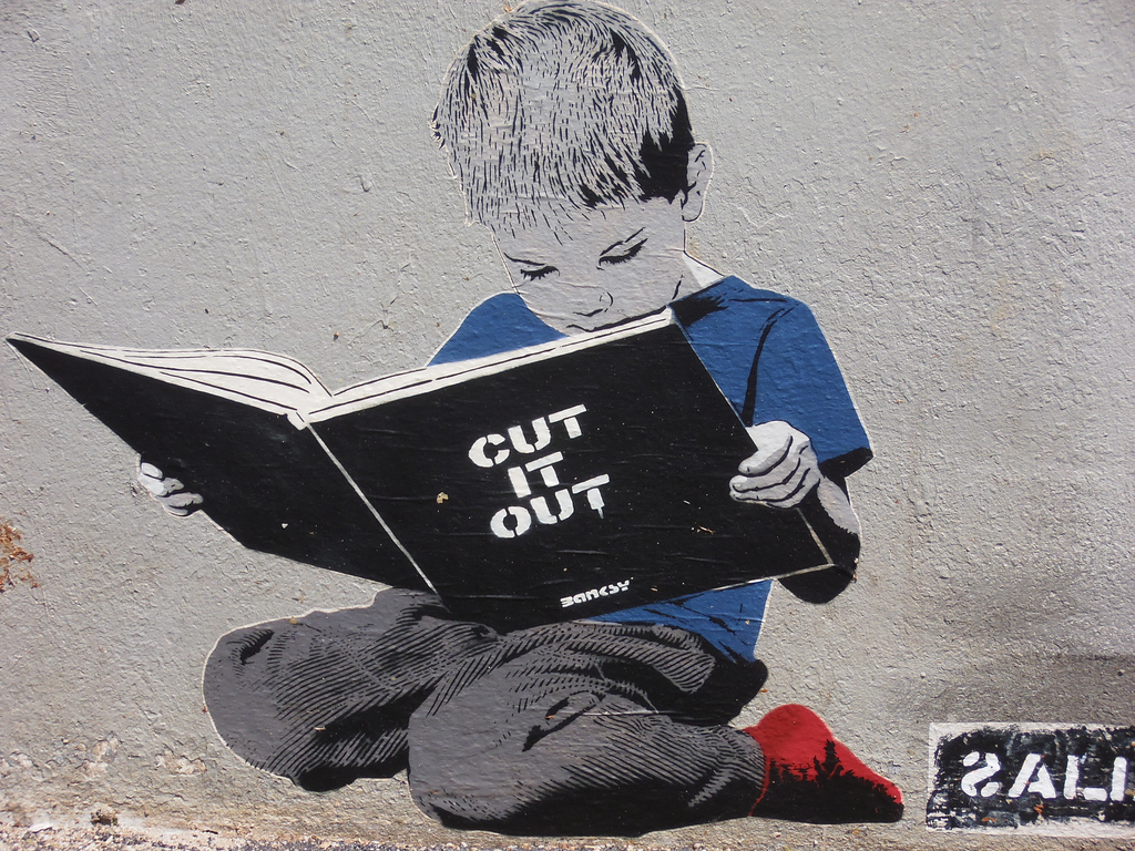 Ménilmontant, Paris. cut it out alias Banksy. A boy's reading