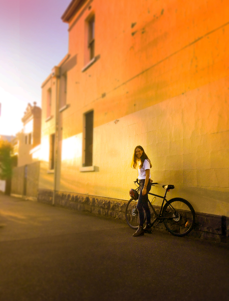 Lea wearne standing next to wall sunset with a bicycle