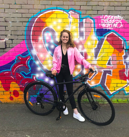 Breanna skewes near graffiti artwork and bicycle