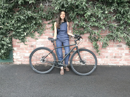 Lea wearne and a bicycle with a brick wall with ivy