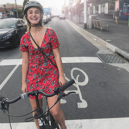 A lady red dress in brunswick on bicycle