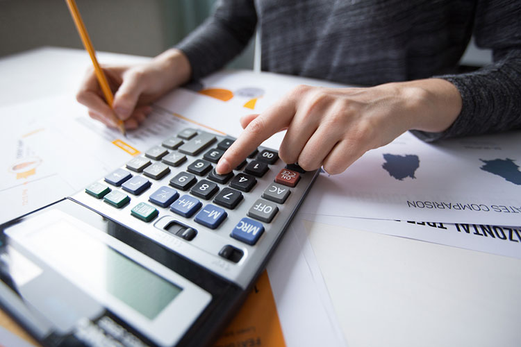 Close-up of female hand counting with calculator, papers all around on table. Businesswoman working with documents