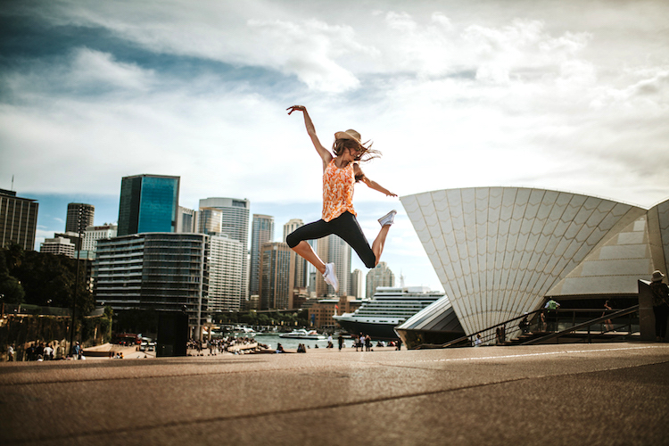 Happy woman jumping in the air in Sydney, with the cityscape in the background.