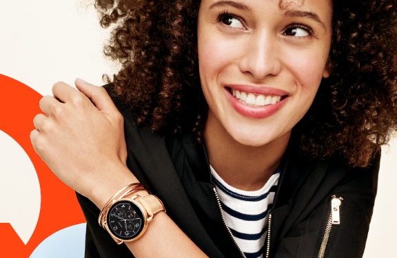 A smiling woman wearing the Fossil Q Wander watch