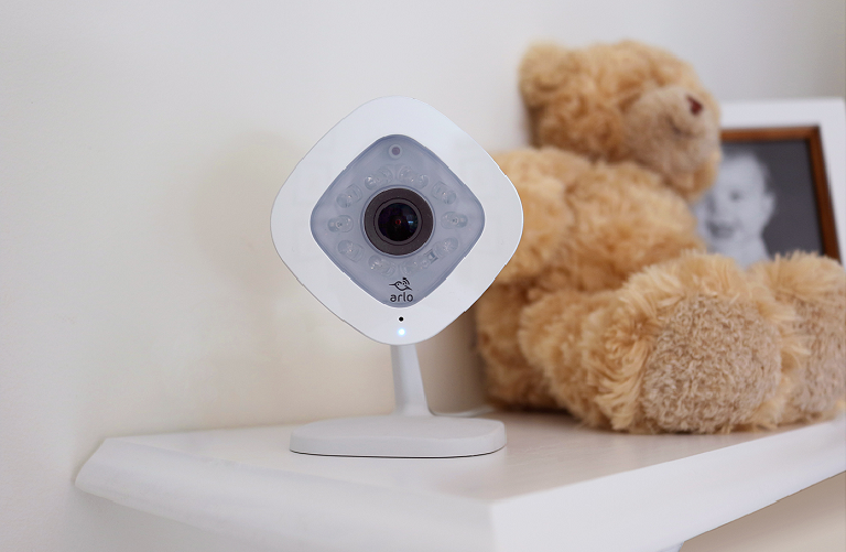 The Arlo Q camera sits on a shelf in a child's room with a teddy bear behind it