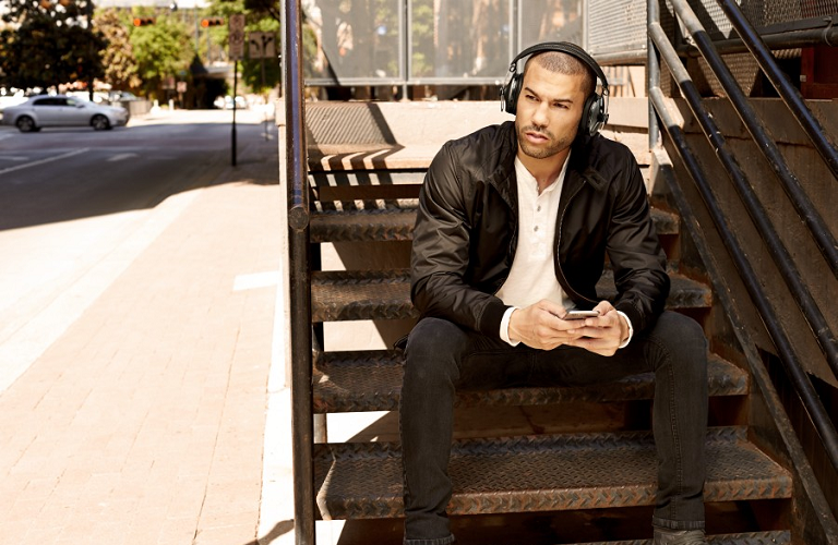A man sitting on stairs outside wearing Momentum Wireless Headphones.