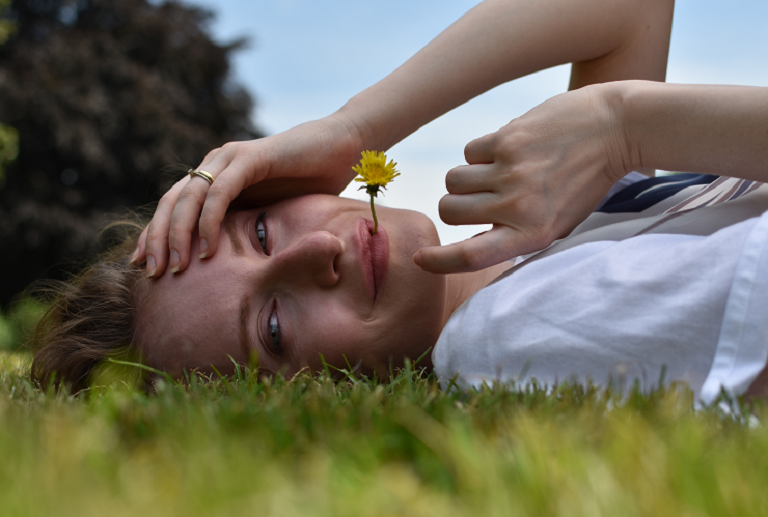 A woman lying on grass with a dandlion between her lips looking at the camera