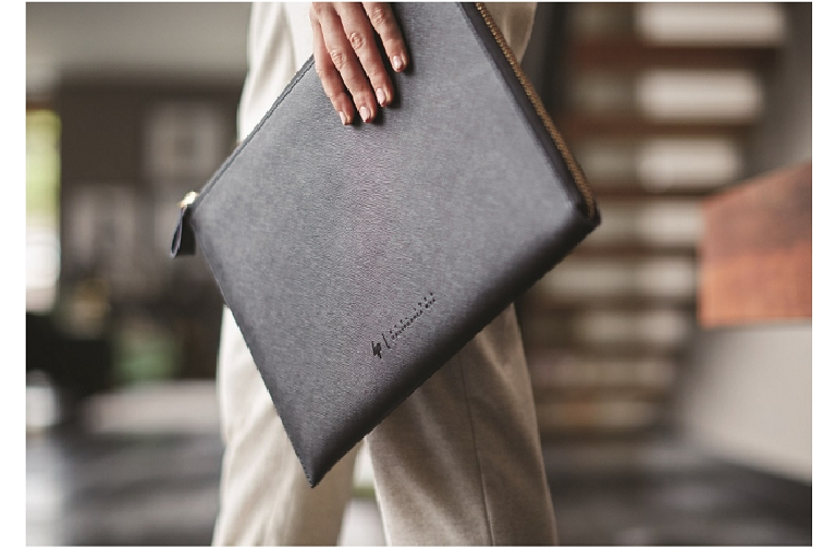 A woman carries the Spectre leather sleeve in her hand