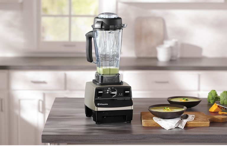 The Vitamix blender on a kitchen bench with bowls of soup