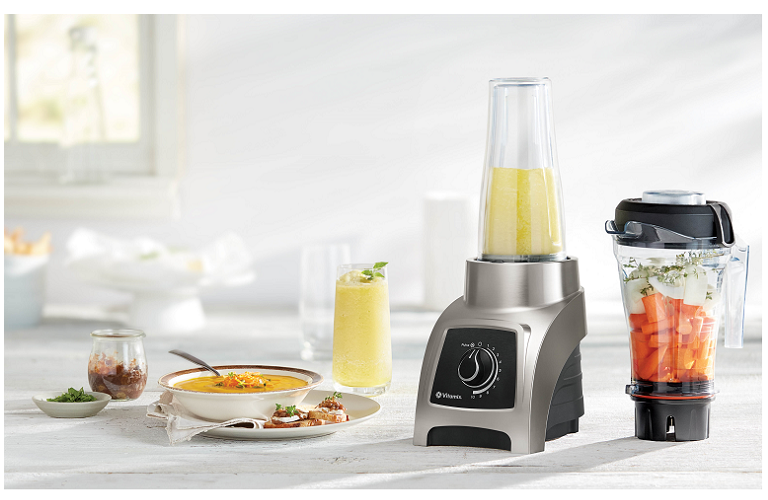The Vitamix blender full of fresh ingredients on a kitchen bench, next to a smoothie and a bowl of soup.