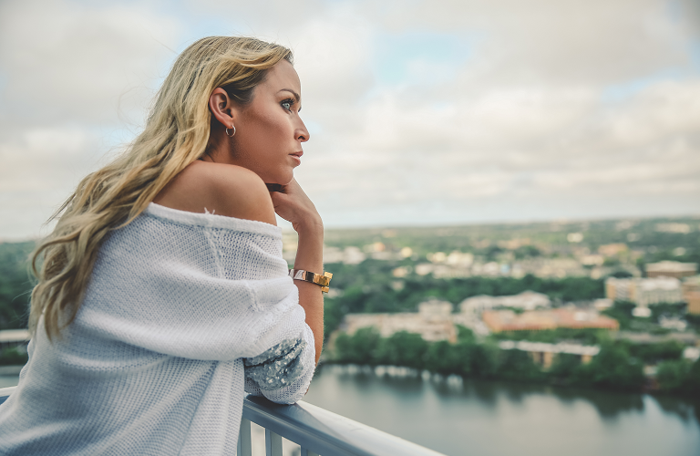 A woman standing on a balcony and looking over a lake while wearing a wisewear activity tracker.