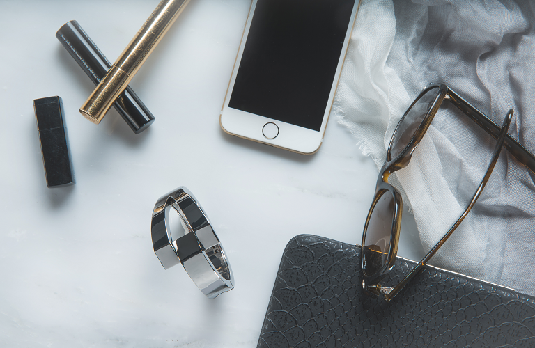 A Wisewear activity tracker beside everyday items such as a phone, sunglasses and lipstick.
