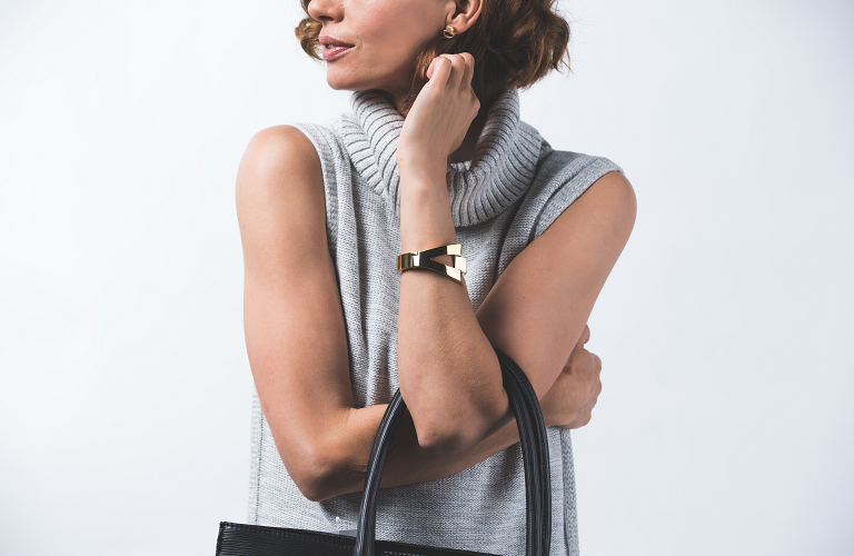 A woman with her arms croseed and holding a handbag while wering a Socilaite activity tracker.