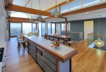 A modern kitchen with an island bench in an open-plan holiday home.