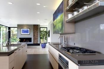A remodeled kitchen featuring white oak cabinets and a panel of contemporary art