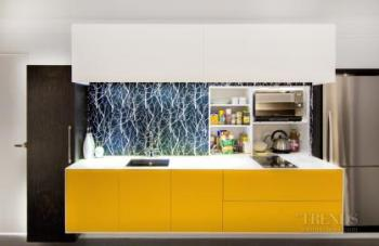 Small apartment kitchen with orange-yellow cabinet and wallpapered splashback