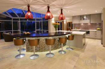 Colourful renovated kitchen with metallic curved island front and red pendants.