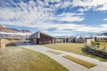 Contemporary rural home with mountain and lake views, schist stone walls, large courtyards